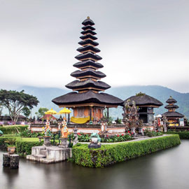 Famous Bedugul temple surrounded by colourful sun umbrellas and translucent volcanic lake