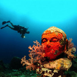 Scuba diver observing with an underwater light excitements of an underwater temple in Bali