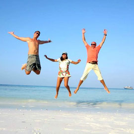 Three adventurous friends joyously jumping in the air on a tropical white sand beach