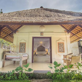 Terrace patio in front of the traditionally built balinese villa showing a comfortable king size bed inside