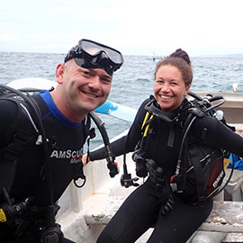 Two scuba diving students in a full diving gear learning good diving skills with a joy and smile.