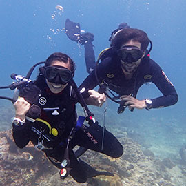 Scuba diving instructor and an excited diving student on his first every try dive